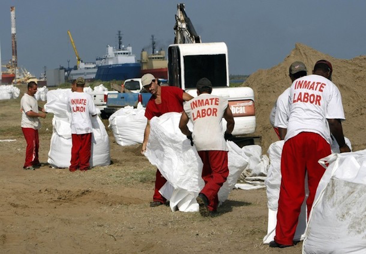 Inmates from a La Fourche parish jail on a work release program fill giant sandbags in Port Fourchon, Louisiana May 11, 2010. U.S. Army National Guard troops were dropping the sandbags using helicopters on nearby breaks in beaches to protect marshes from the BP oil spill offshore. REUTERS/Rick Wilking