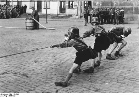 """""""Hitler Youth members playing tug of war while donning helmets and gas masks, 1933"""""""