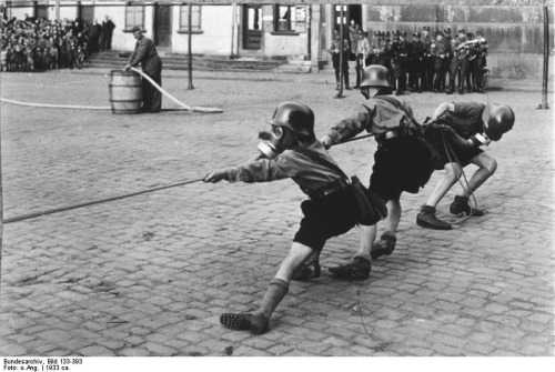 """Hitler Youth members playing tug of war while donning helmets and gas masks, 1933"""